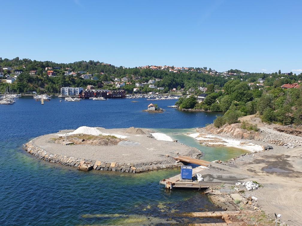 Slik ser det ut på Løkholmen nå. Til høyre i bildet ligger kanalen, med hvite sandstrender på begge sider. Sikringsarbeidet av fjellet bak pågår.